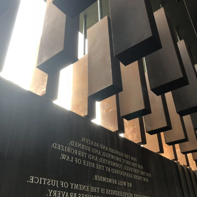 "Image from the National Legacy Museum - shows a wall with the quote ""For the hanged and beaten. For the shot, drowned, and burned. For the tortured, tormented, and terrorized. For the abandoned by the rule of law. We will remember. With hope because hopelessness is the enemy of justice. With courage because peace requires bravery. With persistence because justice is a constant struggle. With faith because we shall overcome."""